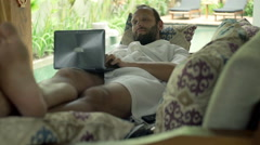 Young man in bathrobe using laptop while lying on sofa in outdoor villa - stock footage