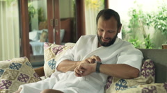 Young man in bathrobe sitting with smartwatch on sofa in outdoor villa Stock Footage
