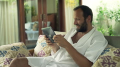 Young man in bathrobe playing game on tablet computer while sitting on sofa in o Stock Footage