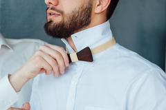 groom wears stylish bow tie using friend - stock photo