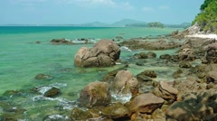 Gentle Waves Lap against Boulders on a Tropical Beach - stock footage