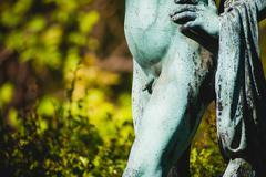 antique statue of naked boy outdoors in nature - stock photo