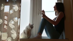 Young woman with tablet and cat on the window-sill - stock footage