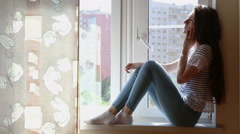 Young woman with smartphone on the window-sill - stock footage