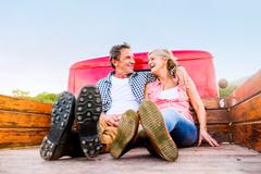 Senior couple sitting in back of red pickup truck - stock photo