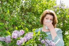 Woman suffering from pollen allergy about lilacs Stock Photos