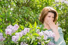 Woman suffering from pollen allergy about lilacs - stock photo