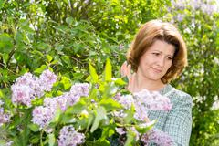 Woman suffering from allergy about lilacs Stock Photos