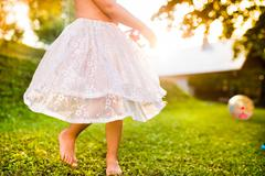 Unrecognizable girl in princess skirt running in sunny garden - stock photo