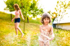 Two girls at the sprinkler, sunny summer in the garden - stock photo