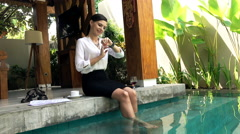 Businesswoman using smartwatch sitting by pool in outdoor villa Stock Footage