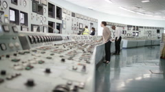 4K Workers in power plant control room, pressing switches on control desk - stock footage