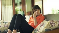 Sad pretty woman watching movie on tablet sitting on sofa in outdoor villa - stock footage