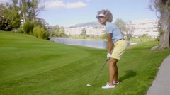 Young woman lining up her golf shot Stock Footage