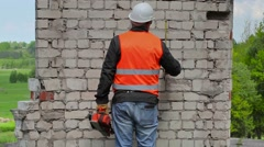 Builder take measurements on the brick wall - stock footage