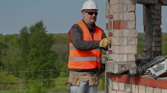 Builder with spirit level near to the unfinished building Stock Footage