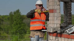 Builder talking on smart phone and using measuring tape - stock footage
