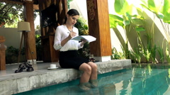 Young businesswoman working with documents sitting by pool in outdoor villa Stock Footage