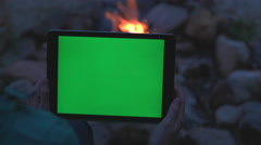 Female Holding Tablet by a Camp Fire with Green Screen. Stock Footage