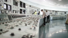4K Workers in power plant control room, pressing switches on control desk Stock Footage