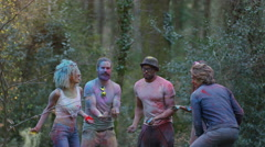 4K Happy hipster friends at music festival, dancing & throwing coloured powder Stock Footage
