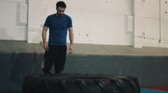 Young man lifting big wheel in bootcamp gym Stock Footage
