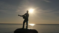 Man with guitar on rock with sea sunset view - silhouette Stock Footage