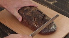 Slicing whole grain bread on wooden table, top view Stock Footage