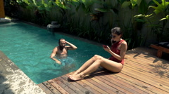 Couple on vacations, woman using smartphone and man relaxing in swimming pool Stock Footage