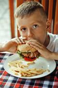 Little cute boy 6 years old with hamburger and french fries maki Stock Photos