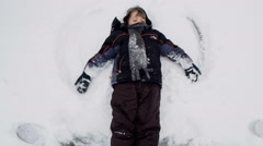 Little Boy Making Snow Angel In Snow Stock Footage