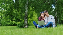 Man and woman relaxing together in the park, working with laptop. They sit on - stock footage