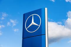 Official dealership sign of Mercedes-Benz over blue sky Stock Photos
