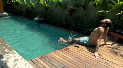 Man relaxing and sunbathing sitting by swimming pool, super sloe motion 120fps Stock Footage