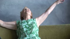 funny elderly woman falls on the sofa after cleaning the house, watching - stock footage