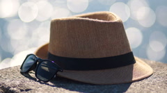 Yellow hat and sunglasses against the background glare of water Stock Footage