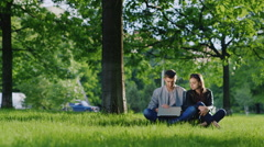 Young couple resting in a park, sitting on the grass and enjoying the laptop Stock Footage
