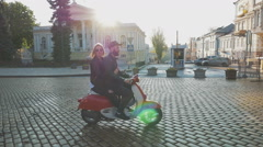 Happy young hipster couple riding a vintage scooter in cit in sun beams - stock footage