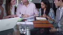 4K Business group in a meeting looking over the company figures - stock footage