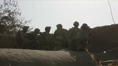 War in Afghanistan - Unit of United States Marines firing at enemy over wall Stock Footage