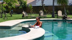 Woman working on her laptop computer sitting at poolside. Beautiful young female - stock footage