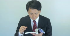 Japanese business suit man reading book excited strong pose  Stock Footage