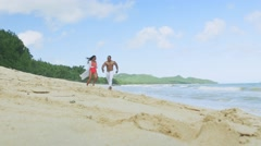 Fit couple playful and flirty at the beach spinning around slow motion Stock Footage