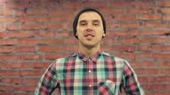 Young blogger in black hat, plaid shirt pronounce words in camera. Brick wall on Stock Footage