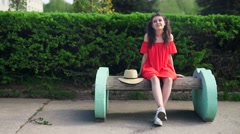 Beautiful happy model standing playful in red dress on nature - stock footage