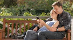 Millennial couple cuddling looking at smart phone device social media - stock footage