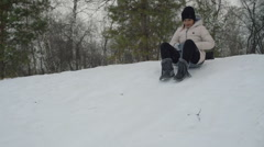 Young asian woman sliding down on snow slowmotion Stock Footage