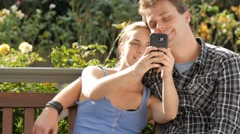 Couple in 20s taking selfie photo with mobile smart phone device laughing Stock Footage