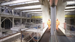 4K Interior view of industrial power plant & engineers walking through building - stock footage