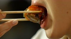 Woman with chopsticks eats sushi. Stock Footage